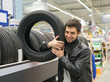 Glad male customer buying new tires in the supermarket. He looks happy