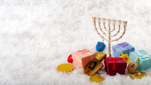 Jewish Holiday And Hanukkah Celebration With Menorah, Dreidel, Gold Coins Or Gelt And Gifts On Snow With Copy Space