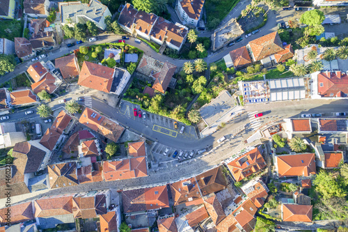 Fototapeta Top view of the city streets with red roofs of houses and highways obraz na płótnie