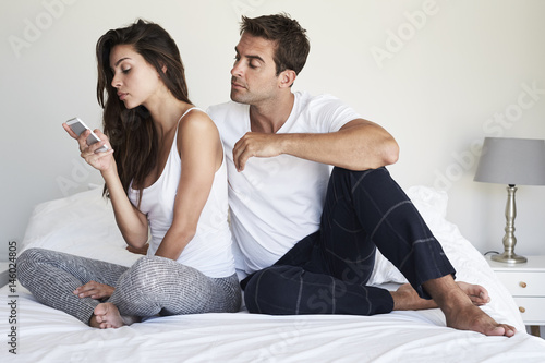 Fototapeta Dude peering over girlfriend's shoulder as she texts