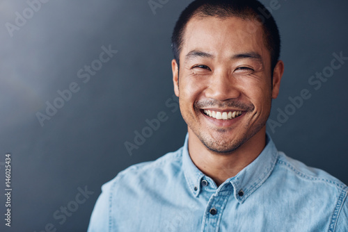 Photo  Smiling young Asian designer standing in an office