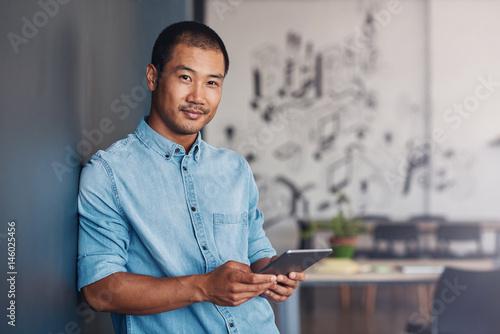 Fotografie, Obraz  Confident Asian designer using a tablet in a modern office