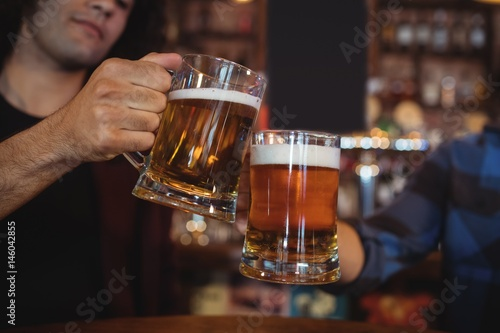 Photo  Two young men toasting their beer mugs
