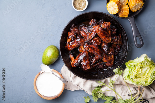 In de dag Grill / Barbecue Chicken wings in thick barbeque sauce with grilled corn, sour cream sauce, honey and salad in black cast iron pan on gray rustic background. Mexican cuisune. Copy space.