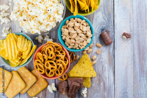 Valokuva  Unhealthy snacks on wooden background