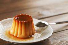 From Above White Plate With Flan And Spoon On The Wooden Background. Horizontal Shoot.