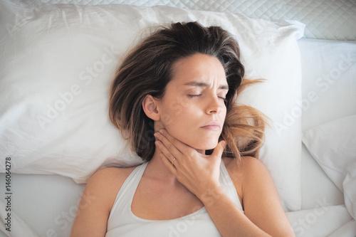 Valokuva  Donna a letto con mal di gola e dolori