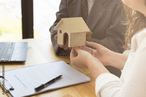 Hands Giving House Model To Other Hands With Agreement On Desk