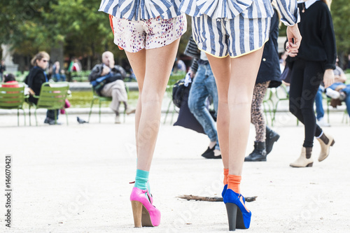 Photo  Legs of two unidentified girls with colorful and fashion high heels shoes walking in Paris during the Fashion Week, France