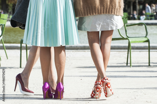 Obraz na plátně Legs of three unidentified girls with colorful and fashion high heels shoes