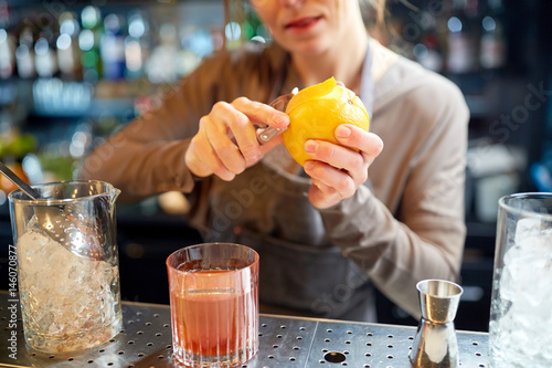 bartender peels orange peel for cocktail at bar Fototapeta