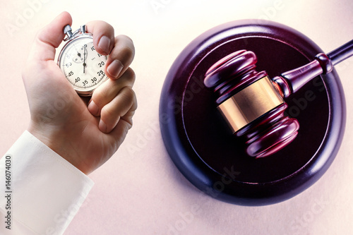 Photo Wooden gavel and stopwatch in male hand
