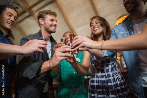 Obraz na plátně  Friends toasting shot glasses in bar