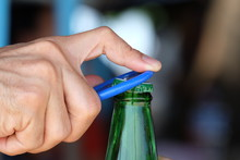 Hand Holding And Opening Cap With Bottle Opener