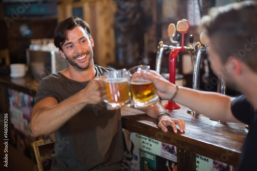 Smiling man toasting beer mug with male friend Canvas Print