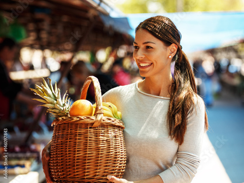 Fotografía  Young woman on street market carrying basket  full of fruits .