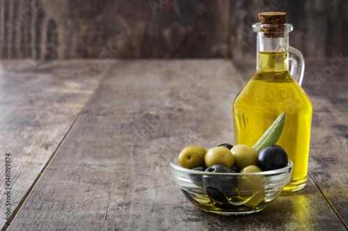 Virgin olive oil in a crystal bottle on wooden background