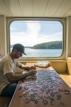 Caucasian Man Assembling Jigsaw Puzzle In Boat Near Window