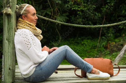 Valokuva  Beautiful young contemplative woman sitting staring at nature