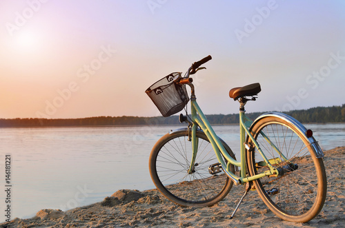 Fotobehang Fiets Vintage bicycle with a basket near the lake during beautiful summer sunset. Copy space.