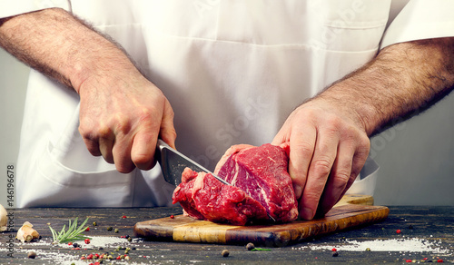 Staande foto Vlees Chef cutting beef meat