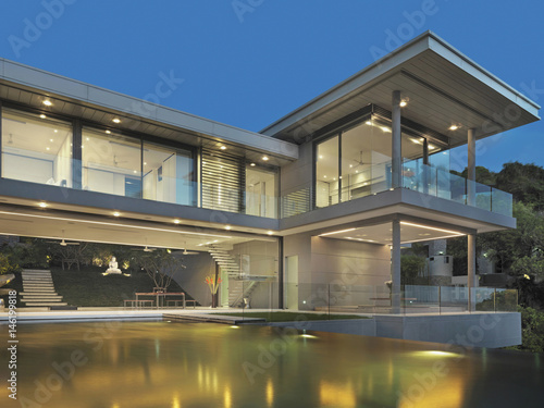 View of multiple story modern home with swimming pool at dusk
