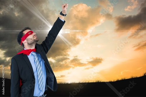 Fotografie, Obraz  Businessman in super hero costume with hand raised against sky