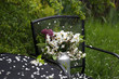 A bouquet of white poetic daffodils and lilacs in a milk can. Spring garden. Dark garden furniture and white petals.