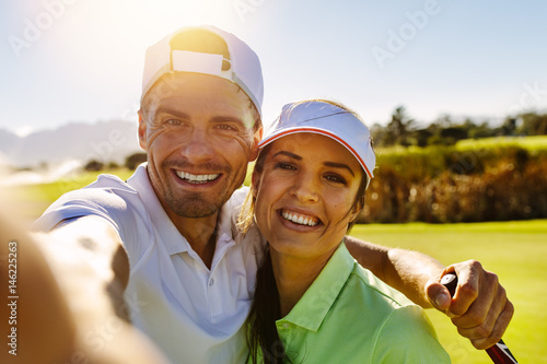 Happy young couple taking selfie at golf course
