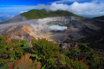 Poas volcano in Costa Rica. Volcano landscape from Costa Rica. Active volcano with blue sky with clouds. Hot lake in the crater Poas. Volcano in Costa Rica. The crater and the lake of the hill Arenal.