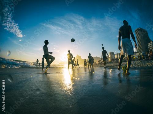 Silhouettes playing beach football on Ipanema Beach in Rio de Janeiro, Brazil
