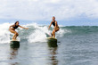 Two girls surfing in ocean
