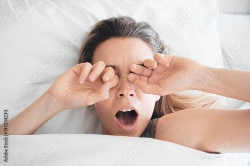 Donna sbadiglia a letto, sonno al mattino Wallpaper Mural