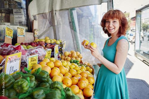 Hispanic woman shopping for lemons at fruit stand
