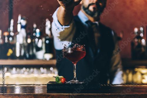 Fotografía  Barman is making cocktail at night club.