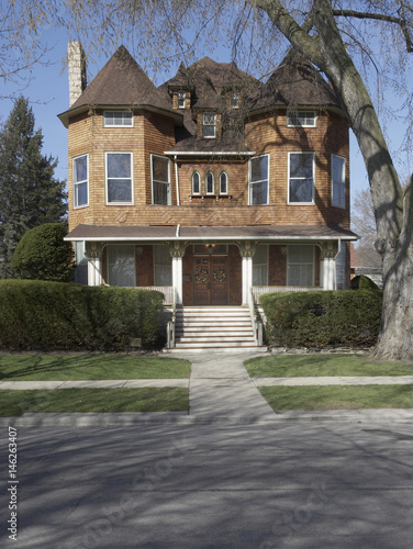 Cedar shake three story home, with gothic windows, and three small dormers, porch with carved fretwork,