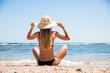 Caucasian woman relaxing on the white sandy beach enjoying the blue sea.