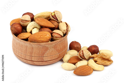 mix almonds, cashew nuts, hazelnut, peanuts, walnuts, pistachio in wood plate isolated on white background