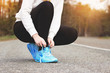 Sporty woman. Portrait of young sports girl tying shoelaces on the road. Healthy lifestyle and sport concepts.