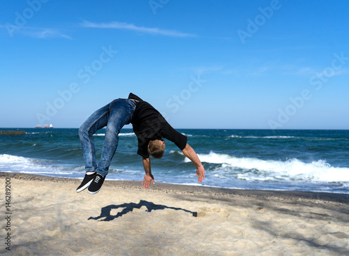0aacbc1af11930 portrait of young parkour man doing flip or somersault on the beach ...