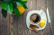Coffee in white cup on wooden table opposite a defocused background with lemon tree.