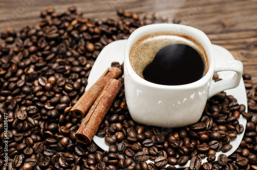 Photo  Coffee cup with beans and cinamon on a wooden table