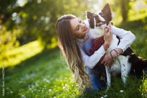 Plakat Piękna kobieta chodzi ślicznego psa w naturze
