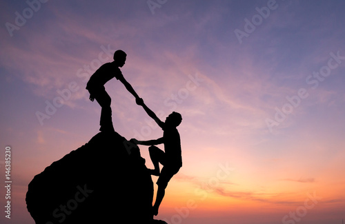 Photo  Teamwork couple hiking help each other trust assistance silhouette in mountains, sunset