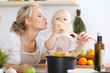 Mother kiss her child daughter while cooking pasta for the breakfast. Concept of happy family in the kitchen.