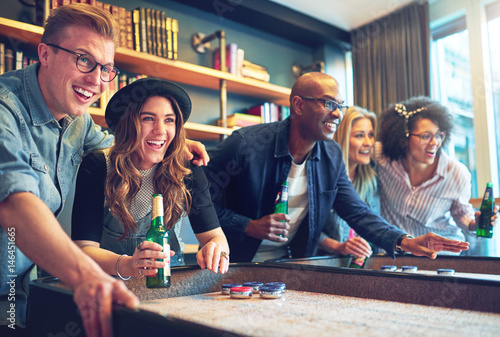 Valokuvatapetti Mixed race friends playing game at bar