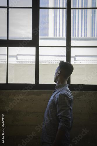 Fotografie, Obraz  Man looking out window