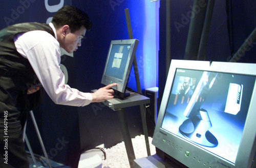 SOUTH KOREAN CUSTOMER EXAMINES A FLAT MONITOR IN SEOUL  - Buy this