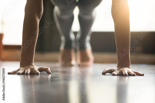 Poster School de yoga Young woman practicing yoga, doing Push ups or press ups exercise, phalankasana Plank pose, working out, wearing sportswear, grey pants, indoor, home interior, living room floor. Close-up of hands