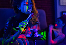 Portrait Of Fashion Model Woman In Uv Neon Light With Fluorescent Glowing Body Art Make-up. She Is Blowing Charcoal From A Hookah. Low Key Dark Image. Soft Focus Image.